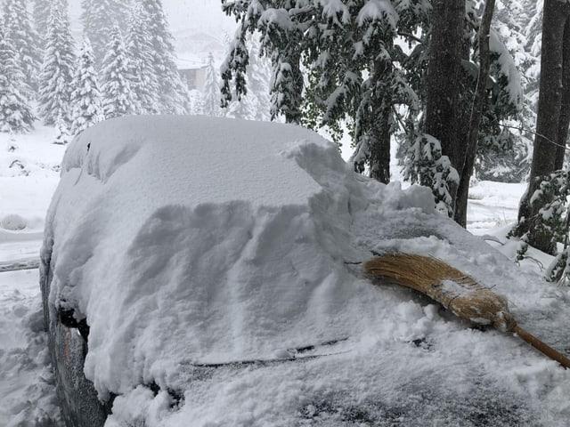 Auf einem Auto liegt noch viel Schnee und ein Besen, der beim Abräumen hilft.