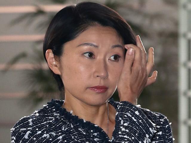 Eine japanische Frau streicht sich das Haar zurück.