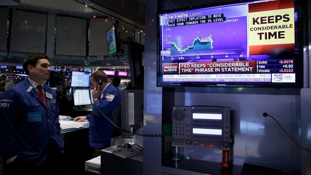 Ein Börsianer schaut einen Aktienkurs auf dem Bildschirm an.