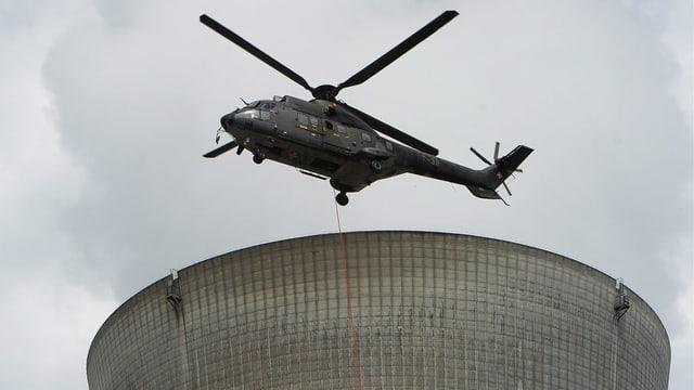 Hubschrauber über Kühlturm von AKW.