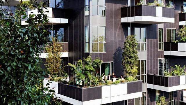 Nahaufnahme der Fassade eines Hochhauses in Mailand, wo Balkone mit Bäumen bepflanzt wurden.