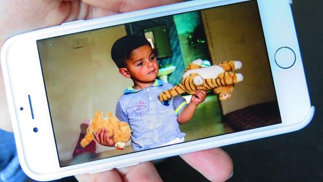 Auf einem Bildschirm ist ein Foto von einem Jungen, der zwei Kuscheltiere trägt.