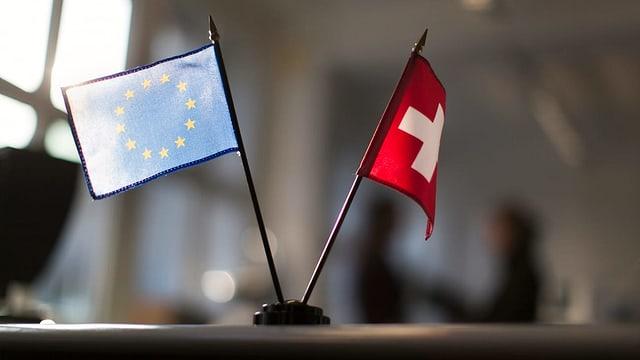Bandierinas da l'UE e da la Svizra sin ina maisa.