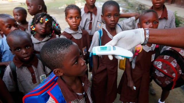 Symbolbild: Kinder stehen in einer Gruppe, eine weiss behandschuhte Hand misst bei einem Kind die Temperatur mit einem Infrarot-Messgerät.
