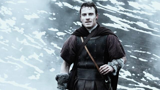 Ein Mann in antiker Kleidung steht in einer verschneiten Berglandschaft.