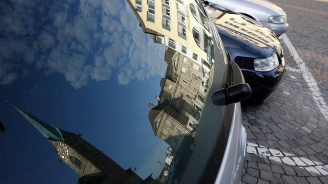 Das Zürcher Fraumünster spiegelt sich auf einem Auto auf dem Münsterhof.