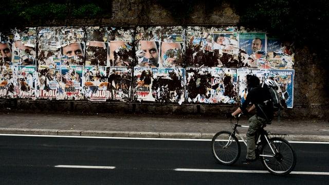 Ein Fahrradfahrer fährt an einer Wand mit Wahlplakaten entlang.