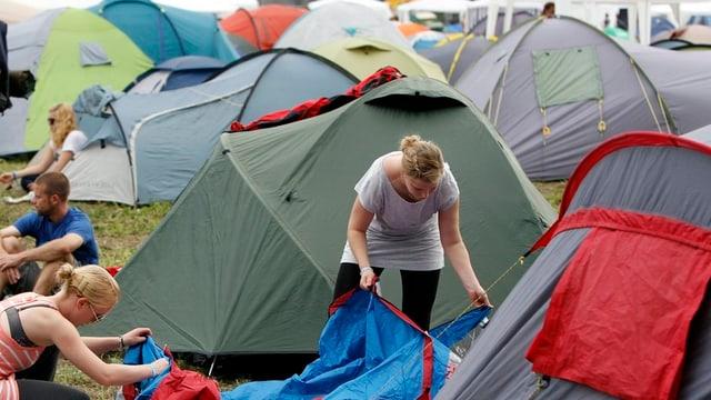 Jugendliche bauen an einem Festival ihre Zelte auf.