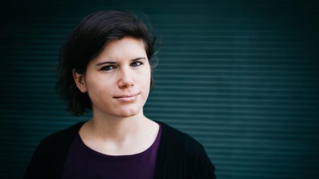 Porträtbild von Ingrid Brodnig vor einer blau-grauen Wand.