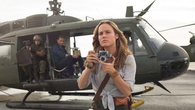 Eine Fotografin vor einem Hubschrauber.