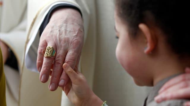 Ein kleiner Junge ergreift die Hand eines Kardinals (Symboldbild).