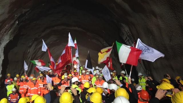 Bauarbeiter in einem Tunnel: Sie schwenken verschiedene Flaggen.