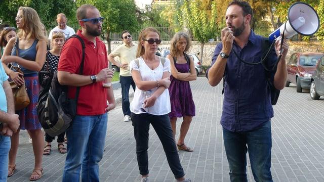 Menschen, die einem Mann zuhören, der ein Megafon trägt.