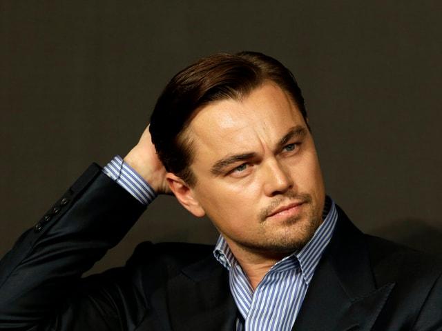 Schauspieler Leonardo DiCaprio stützt mit einer Hand seinen Kopf.