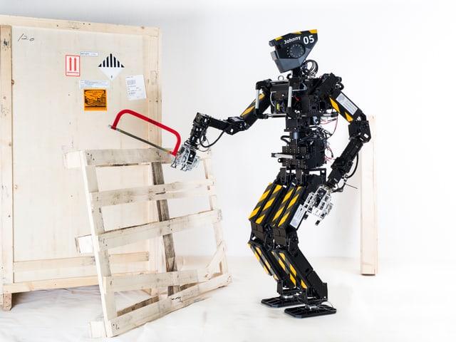 Ein Roboter hält eine Säge an ein Holzbrett.