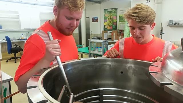 Zwei junge Männer stehen um ein Metallbehälter