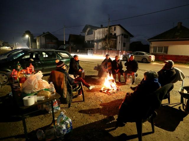 Menschen sitzen um ein Feuer im Freien.