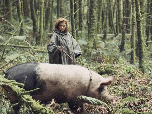 Frau führt ein Schwein an der Leine.