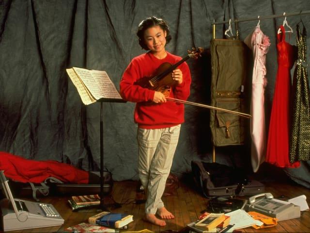 Midori posiert mit Geige als Kind.