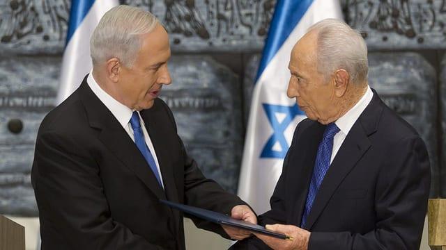 Peres übergibt Netanjahu (links) ein Dokument