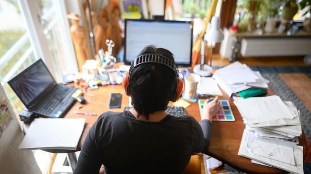 Eine Frau arbeitet zu Hause am Bildschirm.