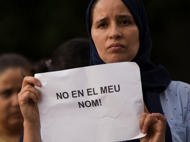 Frau mit Plakat mit der Aufschrift «Nicht in unserem Namen».