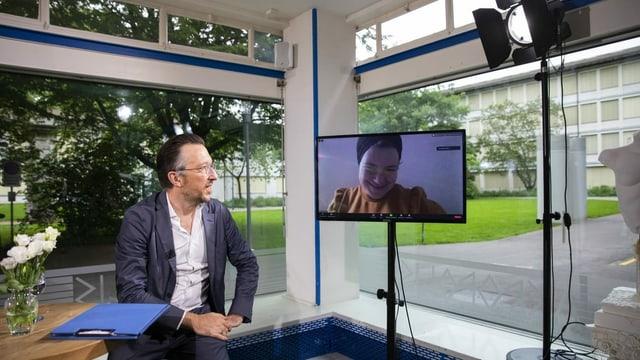 Ein Mann sitzt in einem Raum und blickt auf eine Frau auf einem Bildschirm.