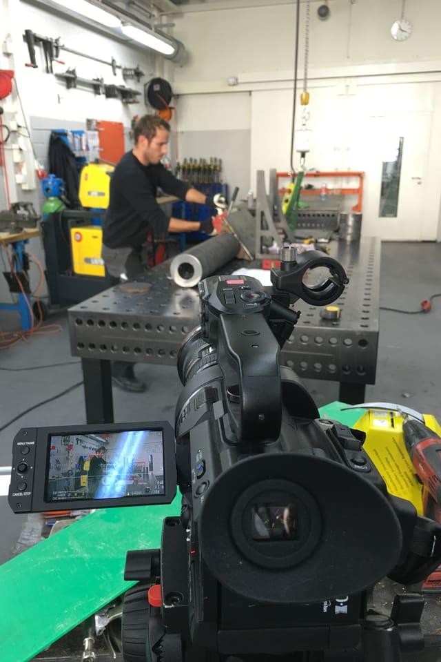 Eine Kamera, dahinter ein Werkbank mit dem Torpedo-Rohr