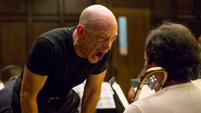 Mann schreit Musiker an.