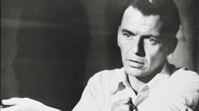 Frank Sinatra bindet sich mit Krawatte den Arm ab.
