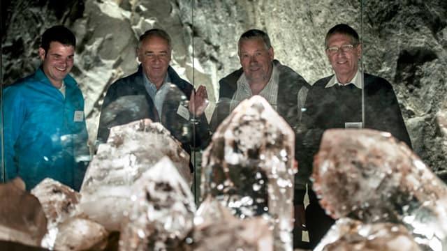 Vier Männer hinter einer Berg-Kristallgruppe.
