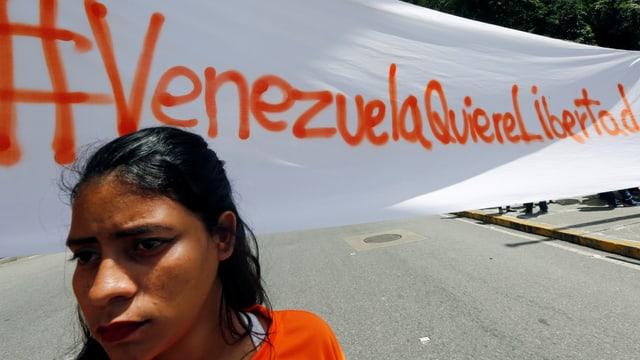 Venezolanische Demonstrantin vor einem Banner