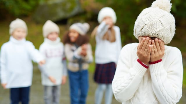Vier Kinder deuten auf ein anderes Kind, das die Hände vor sein Gesicht hält