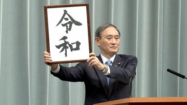 Suga mit der Beschriftung des Reiwa-Zeit in einem Rahmen.