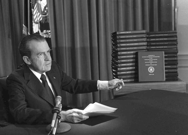 Auf dem Bild ist Richard Nixon neben einem Stapel Transkripte zu sehen.