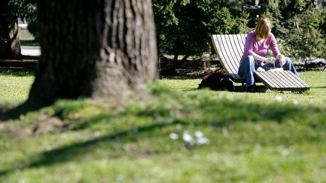 Park mit Baum und Frau auf einer Liegebank.