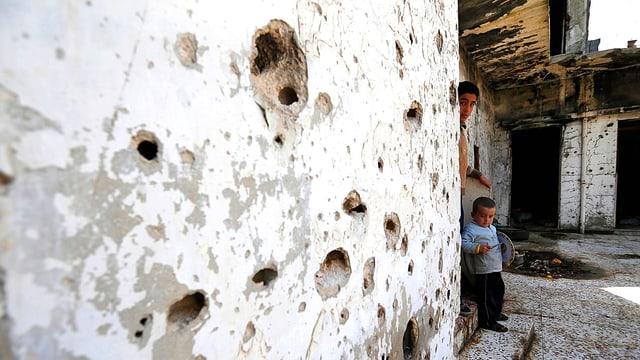 Eine Häuserwand in Aleppo in Syrien. Sie ist von Schüssen durchlöchert. An deren Ende sind ein Mann und ein Kind zu sehen, die beide aus der Ruine nach draussen spähen.