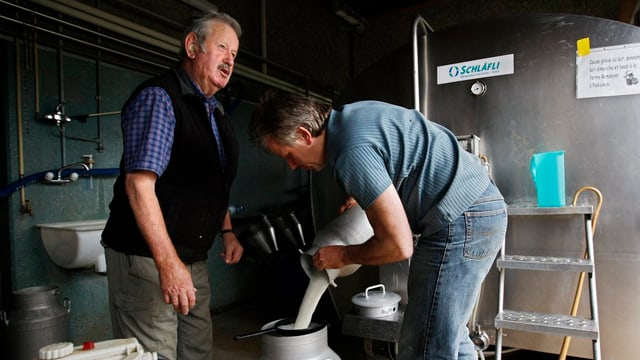 Ein jüngerer Bauer hilft einem älteren beim Abfüllen der Milch.