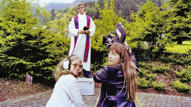 Drei Personen schauen in die Kamera. Zwei Frauen, eine hantiert an der Kamera die andere hat Kopfhörer auf. Sie sind auf einem Filmset, im hintergrund ist ein Pfarrer zu sehen.