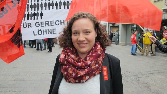 Kantonsrätin Seraina Fürer, dahinter rote Fahnen.