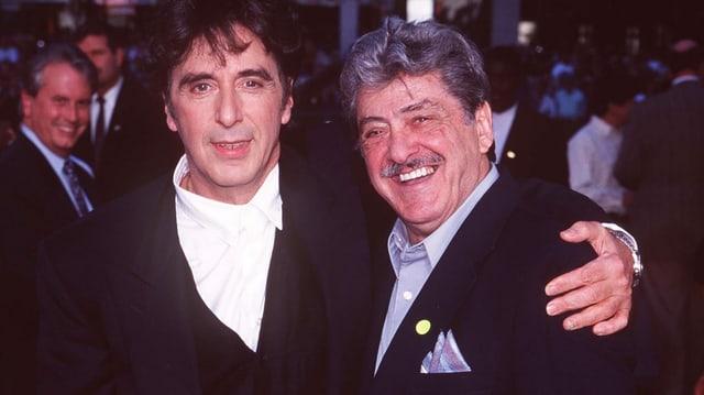 Zwei Männer lachen Arm in Arm in die Kamera.