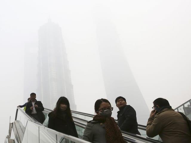 Menschen auf einer Rolltreppe in Shanghai. Zu sehen ist ein dicker Nebel.