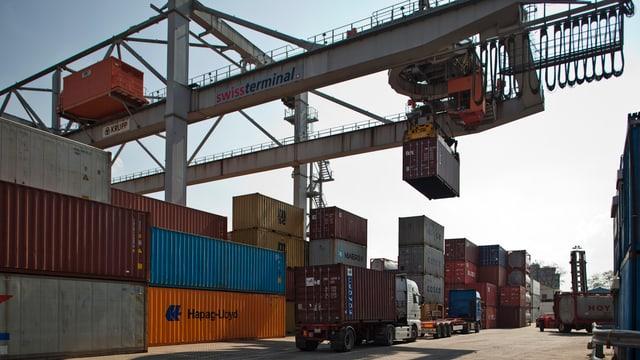 Ein Kran entlädt Container von einem Lastwagen im Hafen Kleinhüningen in Basel.