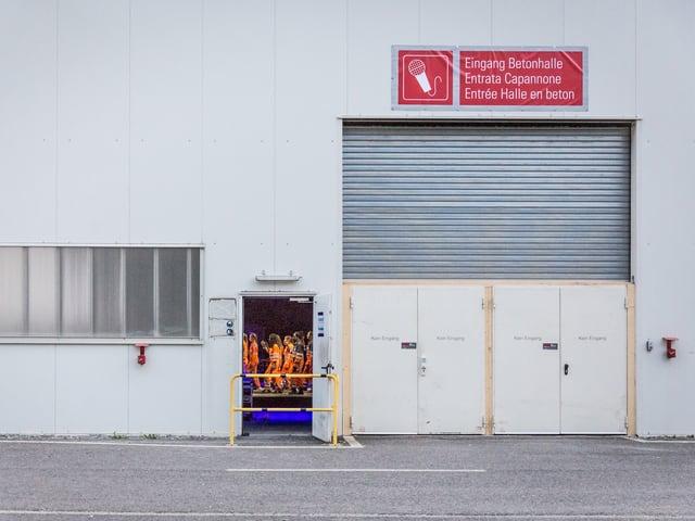 Fassade einer Halle mit offener Tür, durch die man Menschen in orangefarbenen Anzügen sieht.