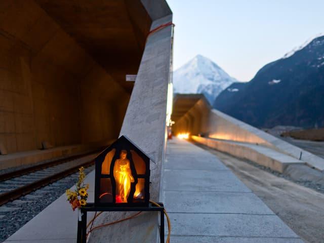 Tunneleingang mit einer beleuchteten Statue in einer Gedenkstätte.