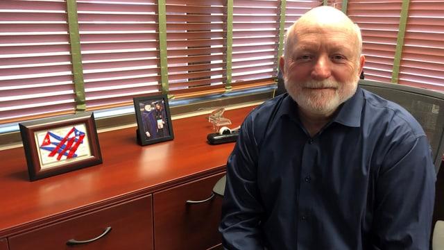 Jorge Duany sitzt neben einem Möbel mit zwei kleinen, gerahmten Bildern drauf.