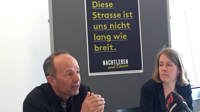 """Wolff und Heeb vor einem Plakat mit der Aufschrift """"Diese Strasse ist uns nicht lang wie breit""""."""