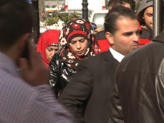 Strassenszene: Im Vordergrund telefoniert ein Mann in Karohemd (abgewandt), rechts zwei Männer in dunklen Anzüge, dahinter zwei Frauen, beide mit farbigen Kopftüchern. ,