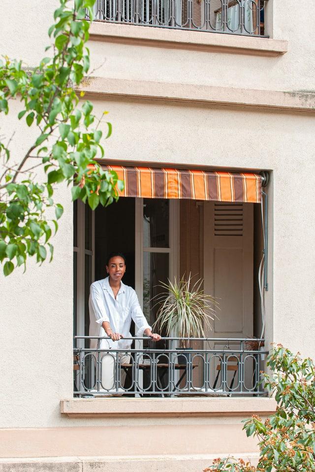 Eine Frau steht auf ihrem Balkon, lächelt.