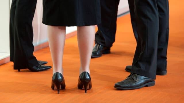 Frauenbeine unter Herrenbeine im Anzug